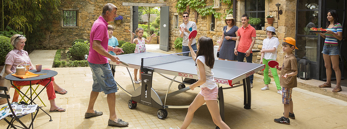 Table Tennis Being Played By Family In The Sunshine